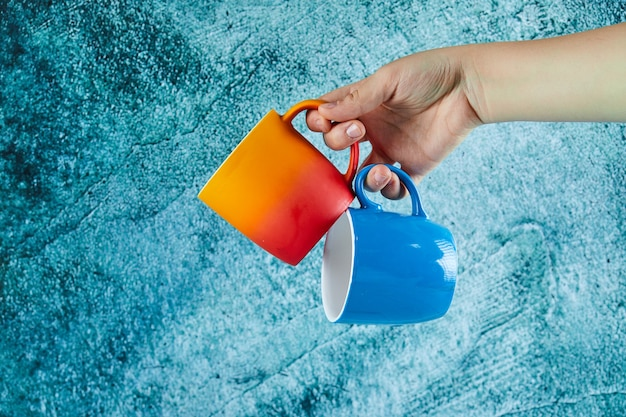 Hand holding two mugs on blue background.