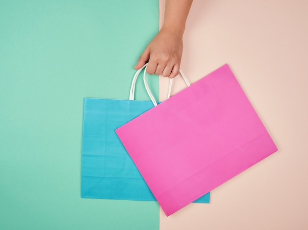 Hand holding two paper shopping bags on a pastel