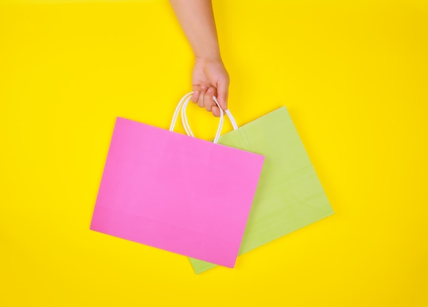 Hand holding two paper shopping bags on a yellow background