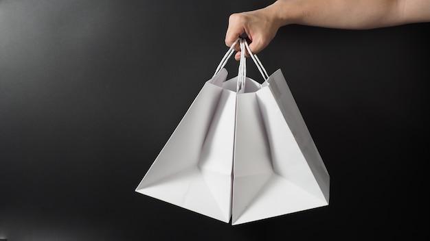 검은 배경에 고립 된 두 개의 흰색 쇼핑 가방을 들고 손.