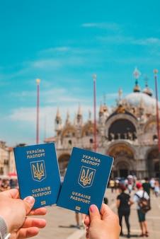 Hand holding ukrainian biometric passports travel concept freedom of movement italy venice