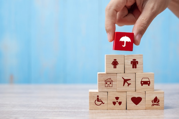Hand holding umbrella wood block cover insurance icon