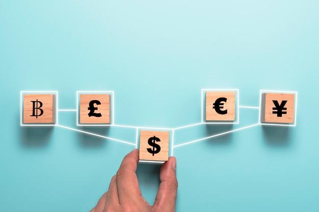 木製の立方体に米ドル記号の印刷画面を持っている手と元の円のユーロと英ポンドとのリンク。外貨両替と外国為替の概念。
