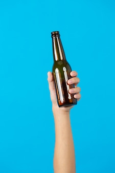Mano che tiene la bottiglia usata su sfondo blu