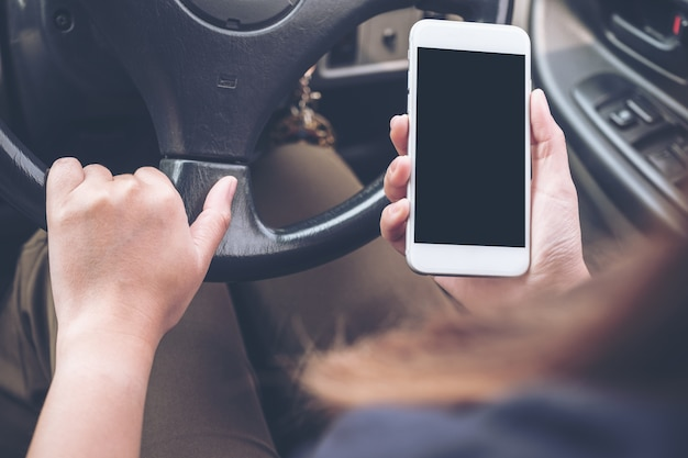 A hand holding and using phone with blank black desktop screen while driving