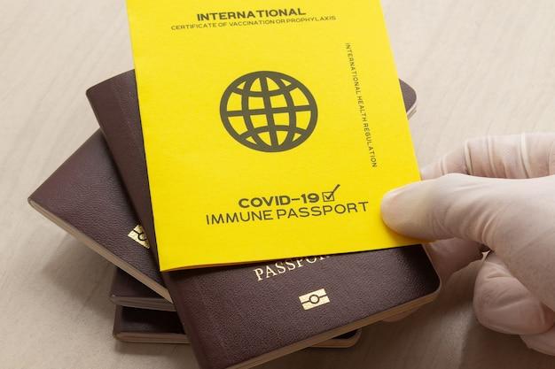 Рука держит паспорт вакцины как доказательство того, что владелец вакцинирован против covid-19, требование для международных поездок.