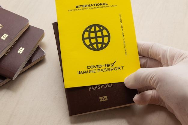 보유자가 covid-19에 대한 예방 접종을 받았다는 증거로 백신 여권을 손에 들고