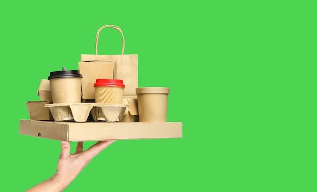 緑の背景にさまざまなテイクアウト食品容器、ピザボックス、ホルダーのコーヒーカップ、紙袋を持っている手。フードデリバリーサービス