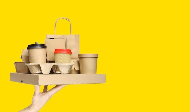 黄色の背景にさまざまなテイクアウト食品容器、ピザボックス、ホルダーのコーヒーカップ、紙袋を持っている手。フードデリバリーサービス