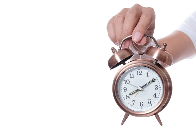 Hand holding vintage alarm clock setting at 7am and showing time over eight o'clock