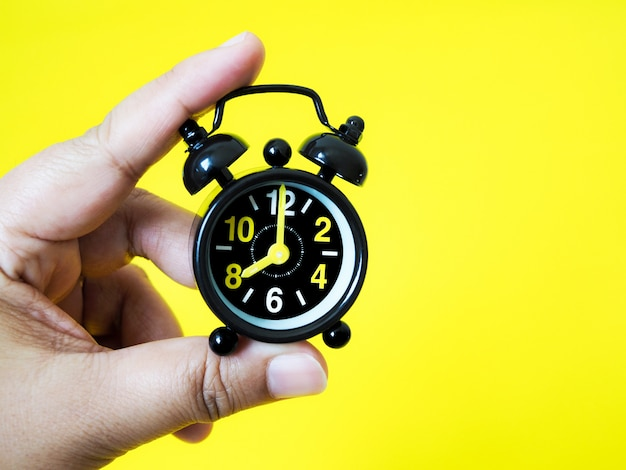 Hand holding vintage black alarm clock on yellow background