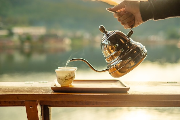 Hand holding vintage teapot and pouring hot tea to cup on wood table against lake view