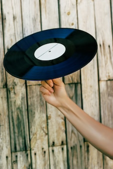 Hand holding vinyl record over wooden background