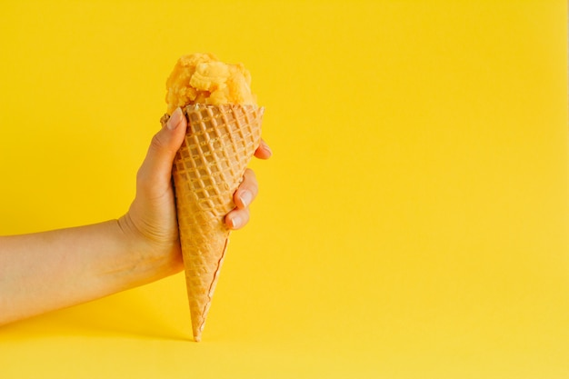 Hand holding waffle cone ice cream isolated on a vibrant yellow, copy space