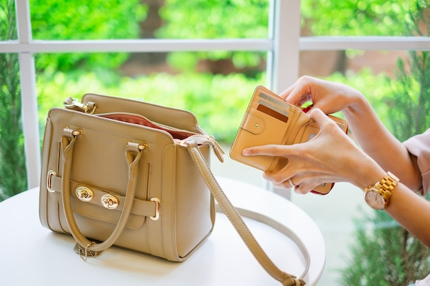 Hand holding wallet with credit card take out money for pay.