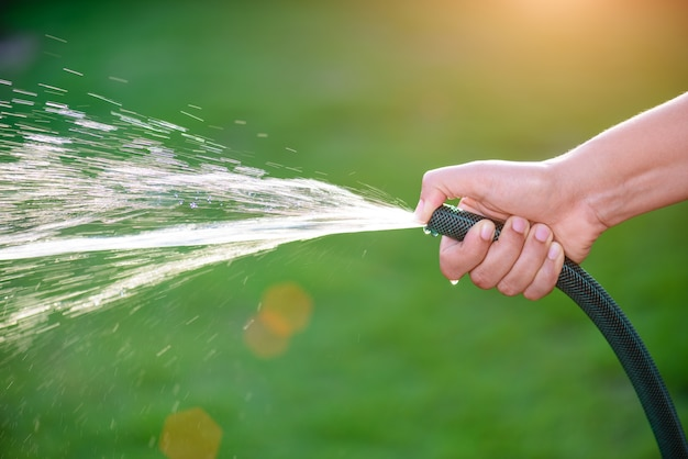 물 호스를 잡고 손가락 끝을 사용하여 햇빛으로 물 스프레이 만들기