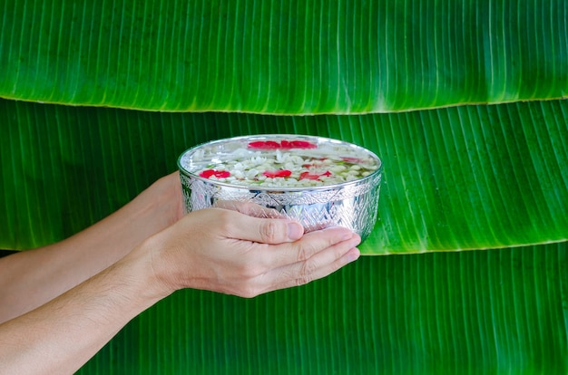 Hand holding water with flowers bowl on wet banana leaf background for songkran festival concept.