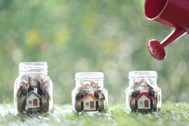 Hand holding watering can with model house and  coin money in the glass bottle on green background