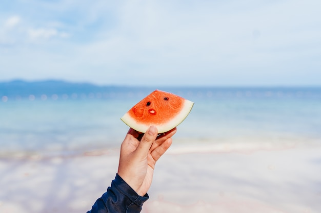 Hand holding watermelon on the beach. watermelon slice in woman hand over sea - pov. summer beach concept. tropical fruit diet.