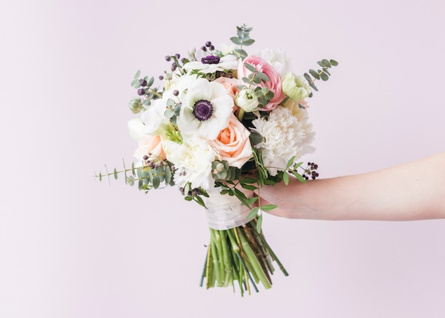 Hand holding wedding bouquet