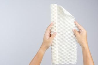 Hand holding white anti slip rubber mat for bathroom or wet floor