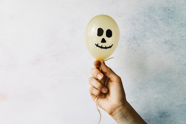 Hand holding white balloon with scary face