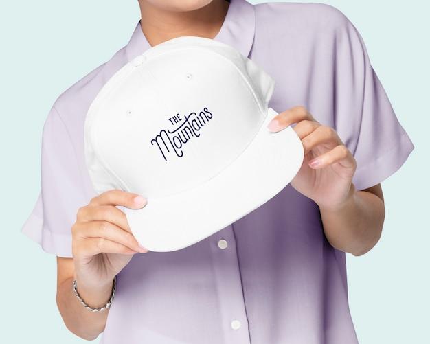 Mano che tiene il berretto da baseball bianco con la stampa del logo delle montagne