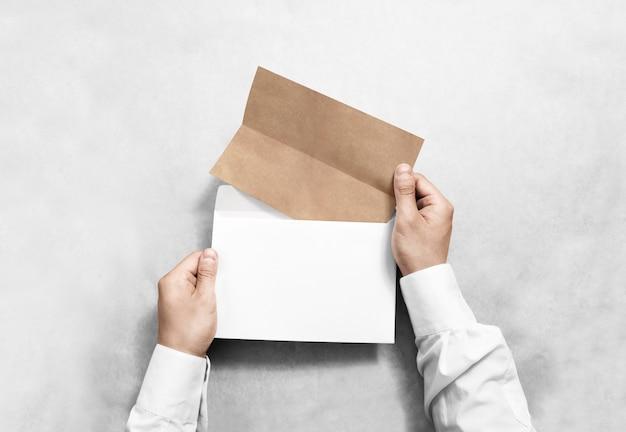 손을 잡고 흰색 빈 봉투와 접힌 된 공예 전단지 프리미엄 사진