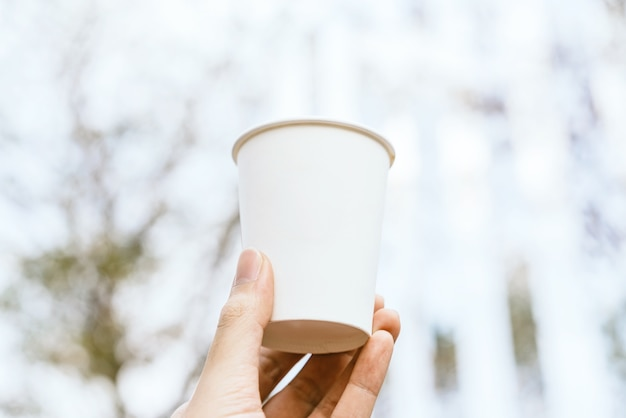 손을 잡고 흐림 흰색 빈 테이크 아웃 종이, 판지 또는 판지 커피 컵.