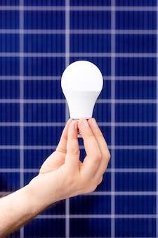 Рука белая лампочка против панели солнечных батарей, солнечной станции. идея концепции альтернативной энергетики, технологий, окружающей среды, экологии. зеленая энергетика.