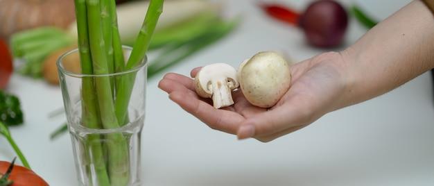 他の新鮮な農場野菜とテーブルに立っている間白いボタンキノコを持っている手