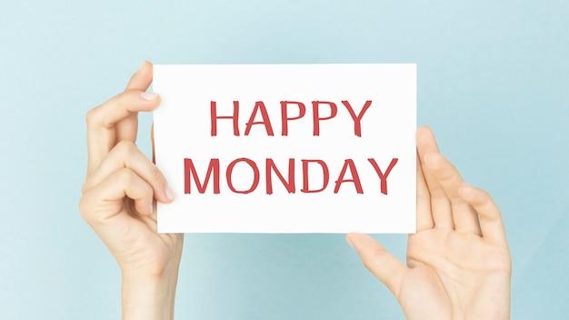 파란색 배경에 흰색 카드를 들고 손-행복한 월요일