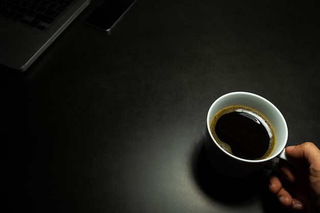 Hand holding a white cup of hot black coffee