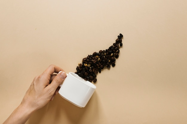 Hand holding white cup with coffee beans