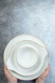 Hand holding white dinnerware set on the bottom on half dark light gray surface with distressed surface
