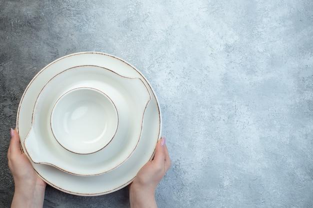 苦しめられた表面を持つ半分の暗い明るい灰色の表面の右側に白い食器セットを持つ手