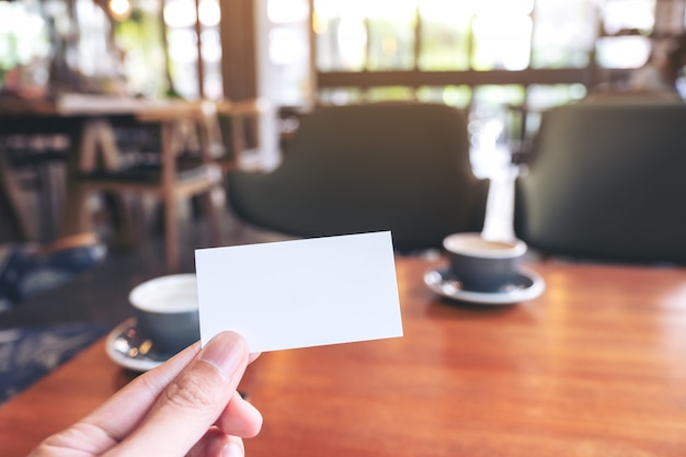 A hand holding white empty business card with two coffee cups on wooden table in cafe