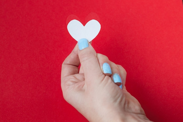 Hand holding a white heart on a red background. background for valentine's day
