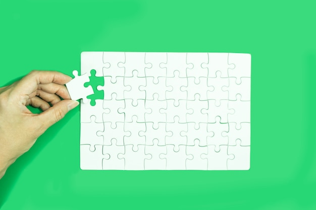 Hand holding white jigsaw puzzle game on green background.