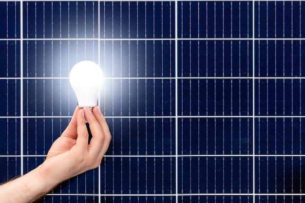 Рука белая лампочка против панели солнечных батарей, солнечной станции. идея концепции альтернативной энергетики, технологий, окружающей среды, экологии. зеленая энергетика. скопируйте пространство.