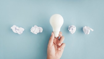 Hand holding white light bulb with crumpled paper balls on gray background