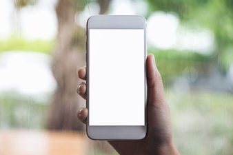 Hand holding white mobile phone with blank desktop screen