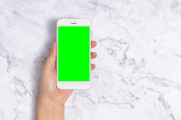 Hand holding white mobile phone with blank green screen