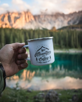 Hand holding a white mug with a blurry mountain landscape as
