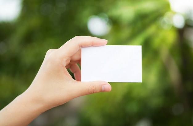 Hand holding a white paper with the background defocused