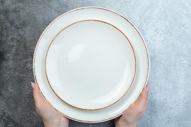 고민 거친 입자 그라데이션 표면과 절반 어두운 밝은 회색 표면에 흰색 접시를 들고 손