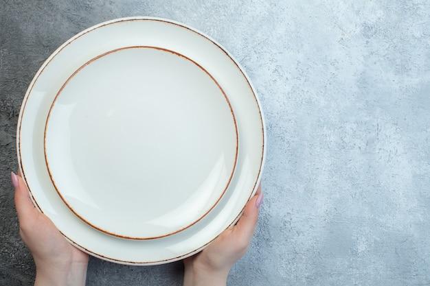 Mano che tiene piatti bianchi sul lato destro su metà superficie grigio chiaro scuro con superficie sfumata a grana grossa in difficoltà