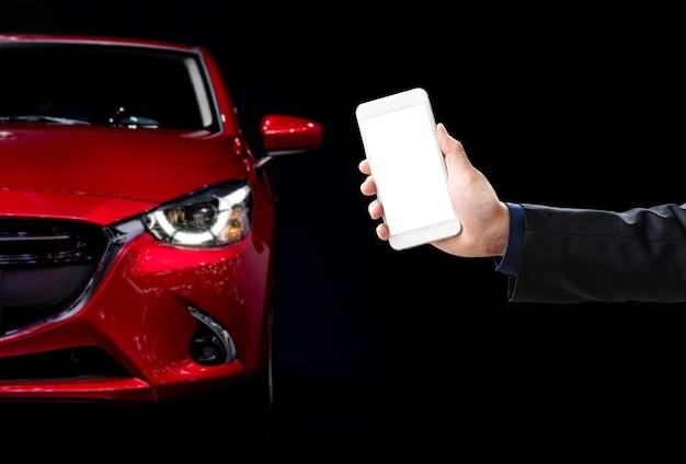 手、車の背景に白い画面の携帯電話を持って