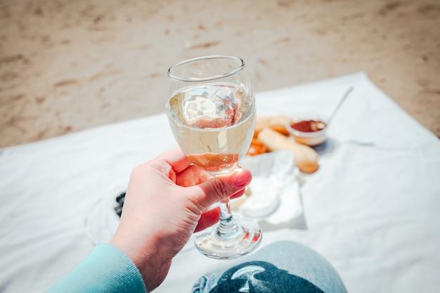 ビーチの背景でピクニックとワイングラスを持っている手
