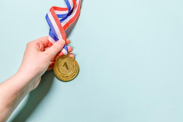 Рука держит золотую трофейную медаль победителя или чемпиона, изолированную на синем фоне